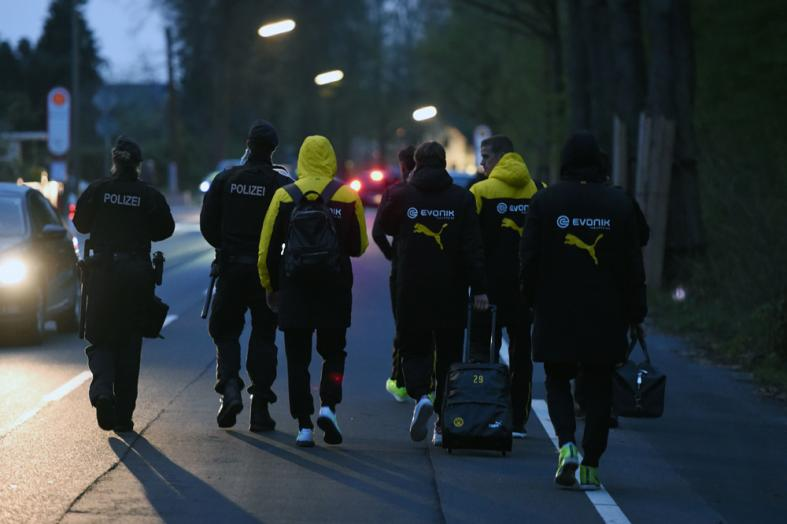 Police escort Dortmund's players after the team bus of Borussia Dortmund had some windows broken by an explosion