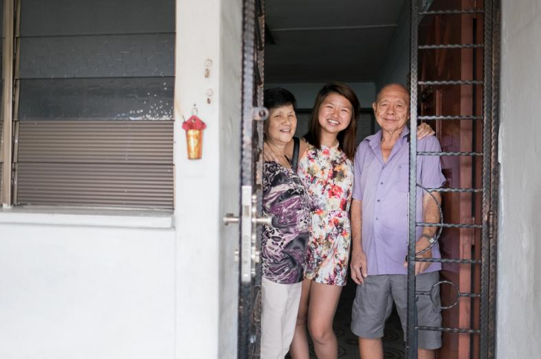 Mr Tan Chai Hock, with his grand daughter Ms Claire Lee and his wife Madam Ong Li Jin at the door of his old flat in Block 1 of the iconic Rochor Centre.