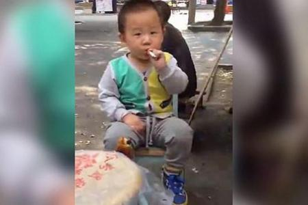 Chinese toddler seen smoking a cigarette while onlookers laugh