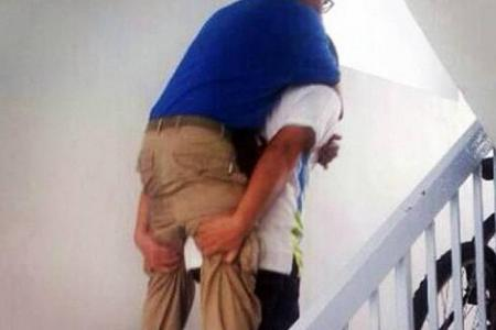 Lift out of order: Town council staff carry resident, who had problems walking, up 10 floors