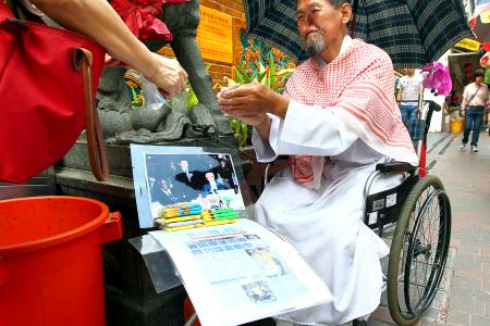 'Parrot Man' now selling tissue paper outside temple