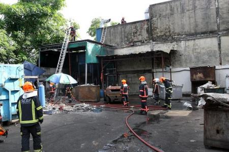 Workers try to put out factory fire