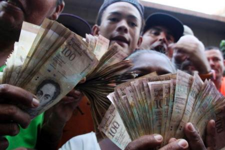 Venezuelans lined up to deposit 100-unit banknotes before they turned worthless, but replacement bills had yet to arrive, increasing the cash chaos in the country with the world's highest inflation