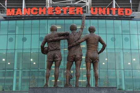 A statue of Manchester United's 'Holy Trinity' of Sir Bobby Charlton, George Best and Denis Law at Old Trafford stadium