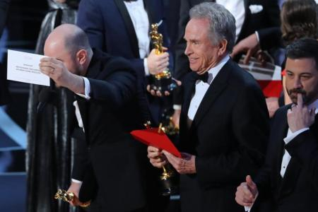 """Jordan Horowitz of """"La La Land"""" (L) holds the card announcing """"Moonlight"""" as the winner of the Best Picture Oscar as presenter Warren Beatty (C) and show host Jimmy Kimmel stand behind."""