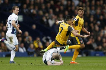Arsenal's Alexis Sanchez sustains an injury after this challenge from West Bromwich Albion's James McClean
