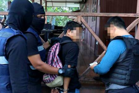 Special Branch Counter Terrorism Division personnel arrest a 24-year-old resort worker in Kota Tinggi.