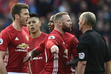 Manchester United's Wayne Rooney and Michael Carrick talk with referee Mike Dean