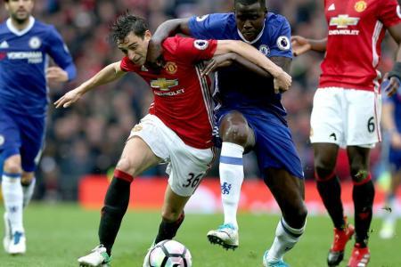 Manchester United's Matteo Darmian (L) challenges Chelsea's Kurt Zouma