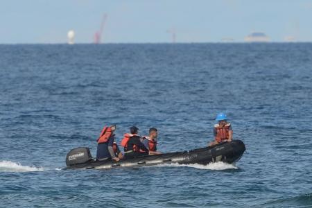 Philippine coast guard officers survey the seas near Thitu island during a visit by Defence Secretary Delfin Lorenzana yesterday.
