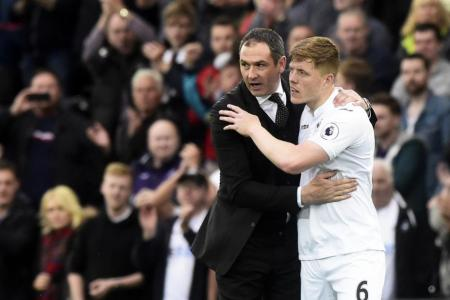 Swansea City manager Paul Clement and Alfie Mawson embrace at the end of the match