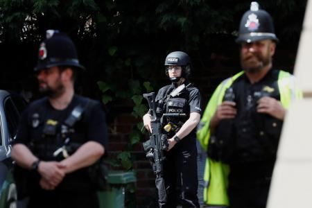Armed and uniformed police officers stand outside a residential property near to where a man was arrested in the Chorlton area of Manchester