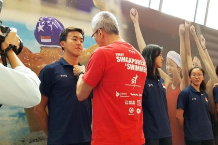 Swimmer Quah Zheng Wen receiving a Singapore flag pin from his father,