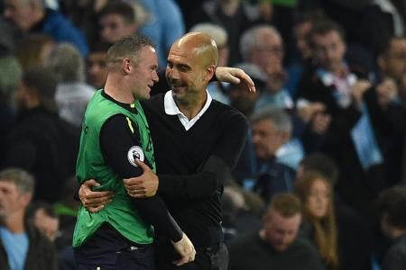Manchester City manager Pep Guardiola and Everton's Wayne Rooney chat