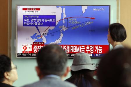 South Koreans watch a television displaying news broadcasts reporting on North Korea's latest ballistic missile launch,