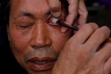 Street barber performs traditional eyelid shave