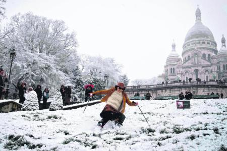 Skiers take to Paris streets as snow prompts travel chaos