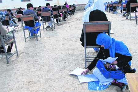 Afghan mother of three writes exam with baby on her lap