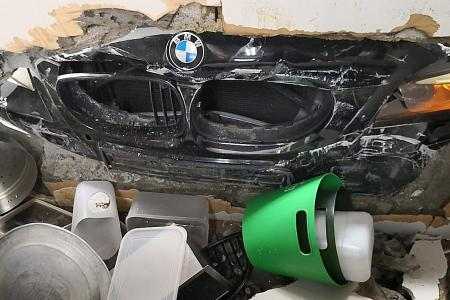 BMW crashes into carpark gantry, two cars and smashes hole in wall