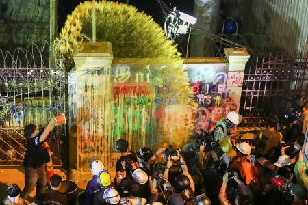 Thai protesters hit police HQ with paint, projectiles