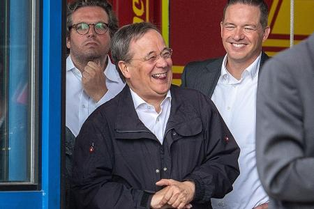 German state premier says sorry for laughing while at flood-hit town