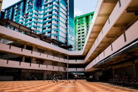 A coffee shop assistant chasing a flock of pigeons at the central concourse in Rochor Centre