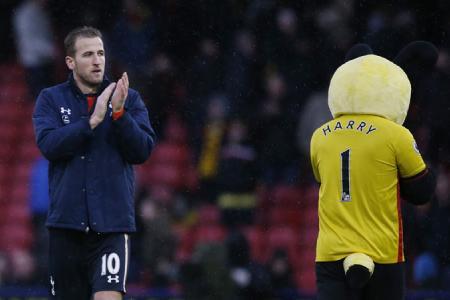 Tottenham's Harry Kane applauds fans while Watford's mascot walks away