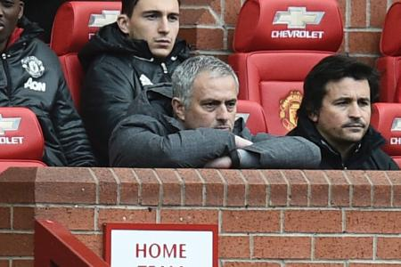 Jose Mourinho watches from the dugout seated next to Manchester United's Portuguese assistant manager Rui Faria