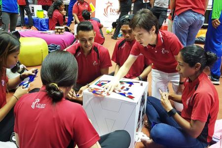 Minister for Culture Community and Youth Grace Fu (kneeling) interacts with able-bodied and para-athletes at the Team Singapore camp at the Singapore Sports Institute in Kallang, before launching the #OneTeamSG Ready for KL campaign.