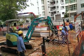 DISRUPTION: (Above) PUB personnel turned off the mains to do repairs. (Left) Mr Zul Hussein (centre) was one of the residents who had no water at home. FOUNTAIN: A water pipe burst after it was struck by a pile operator.
