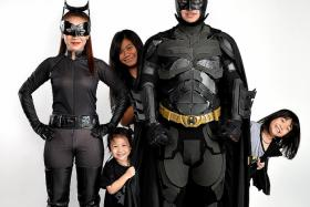 GOING BATTY: Mr Khoo with his wife Nonnicha Prabalee as Catwoman. Behind him is oldest daughter Suputcha Khoo, 13, Khoo Zhi Xuan, six (on his left), and Khoo Le Xuan, three.