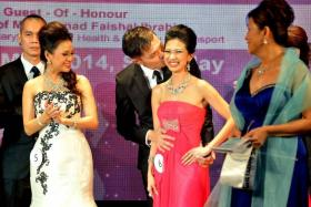 SEALED WITH A KISS: (Above) Madam Cheryl Ho, 32, a finalist, receiving a kiss on the cheek from her husband when her name was announced. - TNP PHOTO: ARIFFIN JAMAR