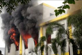 Smoke and flames billow from a factory's building in the Binh Duong province, Vietnam