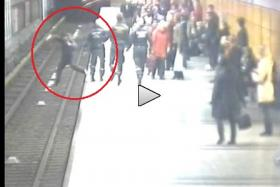 Distracted man accidentally falls off platform onto train track. Fortunately, he's saved by a transit officer in the nick of time.