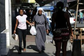 A woman walks with a nun at the Mare slums complex in Rio de Janeiro. An international association of Catholic nuns launched a public awareness campaign to combat prostitution  during the World Cup