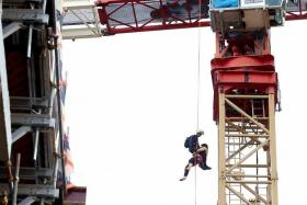RESCUED: A member of the Dart team lowering the weak crane operator to safety.