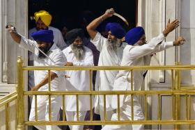 Sikhs wield swords during their clash inside the complex of the holy Sikh shrine, the Golden Temple, in the northern Indian city of Amritsar on Friday.