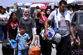 Iraqi families fleeing violence in the northern Nineveh province gather at a Kurdish checkpoint in the autonomous Kurdistan region.