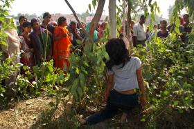 Onlookers look at the body of a woman, hung from a tree, in Moradabad district in the northern Indian state of Uttar Pradesh June 12, 2014.
