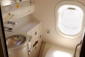 A man was trapped in a plane toilet for more than an hour after accidentally trapping his middle finger in the rubbish bin.