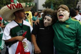 Mexican soccer fans, two of the wearing masks of Mexico's coach Miguel Herrera (right) and goalkeeper Guillermo Ochoa (centre), celebrate the goalless draw at the Angel of Independence monument in Mexico City. Photo