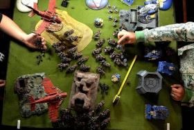 BATTLE FIELD: Players taking turns to move their troops across a large table set up to resemble a war-torn landscape.