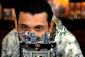 VIRTUOSO: Mr Daniel Levinge with custom-painted Space Marines (above), and the mountainside landscape he is now working on.
