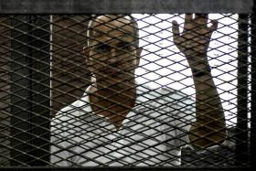 Al-Jazeera news channel's Australian journalist Peter Greste listening to the verdict inside the defendants cage during his trial for allegedly supporting the Muslim Brotherhood.