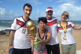 """The New Paper's David Lee (second from left) with soccer fans in Brazil, holding the """"World Cup trophy""""."""