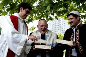 (From left) Pastor Gregor Hohberg, Rabbi Tovia Ben-Chorin and Imam Kadir Sanci holding bricks in the vacant lot where they hope to build a multi-faith prayer building. The House of One in Berlin will have a church, a mosque and a synagogue, along with a common area, where people of all faiths can interact.