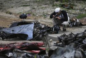 A US forensic expert taking pictures of the wreckage of the car used in the bombing of the business district in Abuja. Photo: