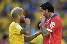 Brazil press officer Rodrigo Paiva has been suspended for allegedly throwing a punch at Chile striker Mauricio Pinilla (right) during their Round of 16 match on Sunday morning.