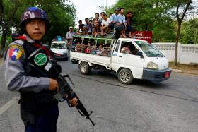 A policeman standing on guard in Mandalay on Friday as tension grips Myanmar's second-largest city.
