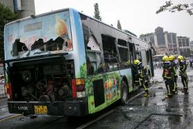 Firefighters inspecting a burnt-out bus on a street in Hangzhou, Zhejiang province on July 5. At least 32 people were injured after the bus was set on fire.